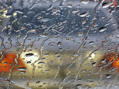 Rainy windshield (shallow depth of field) in morning rush hour